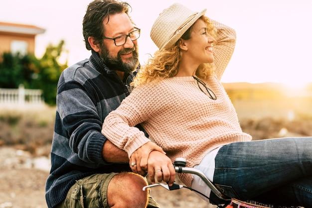 Gelukkige volwassen mensen vrolijk paar genieten van de outdoor vrijetijdsbesteding samen fietsen man dragen vrouw en lachen veel in vriendschap en relatie - actieve jeugdige personen