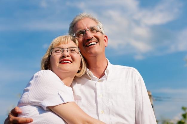 Gelukkige volwassen paar al met pensioen - op zoek naar de blauwe lucht in de zomer