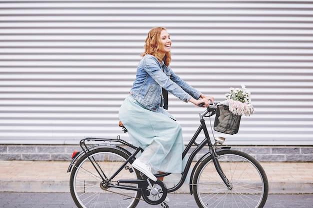 Gelukkige volwassen vrouw die geniet van het fietsen