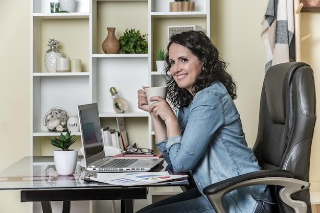 Gelukkige volwassen vrouw die koffiepauze heeft terwijl thuis het werken aan laptop met rapporten