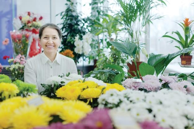 Gelukkige volwassen vrouw in bloemenwinkel