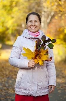 Gelukkige volwassen vrouw in het herfstpark