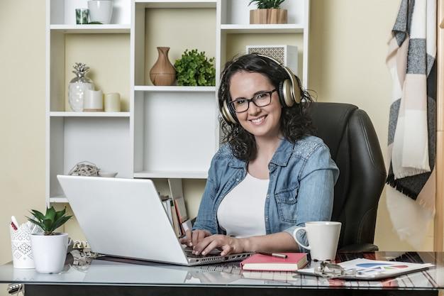 Gelukkige volwassen vrouw in hoofdtelefoons die laptop met plezier thuis met behulp van