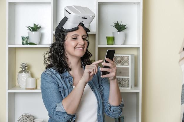 Gelukkige volwassen vrouw in virtuele werkelijkheidsglazen die smartphone thuis gebruiken