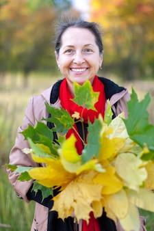Gelukkige volwassen vrouw met maple posy