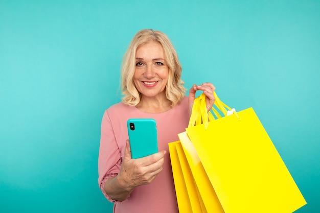 Gelukkige volwassen vrouw op het blauwe achtergrond stellen met gele zakken en heldere telefoon.