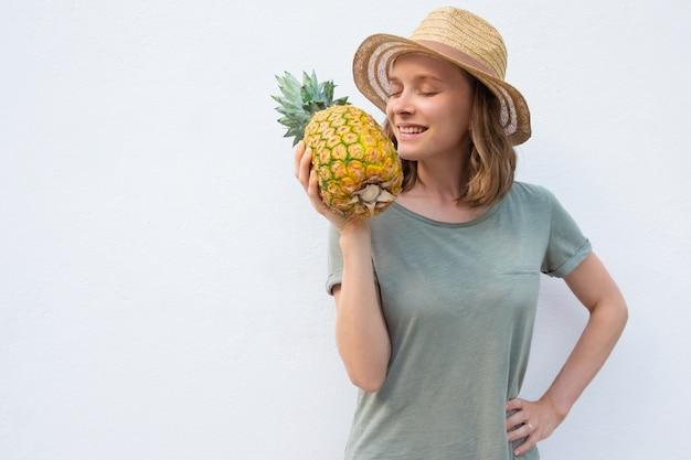 Gelukkige vreedzame vrouw die in de zomerhoed gehele ananas ruikt