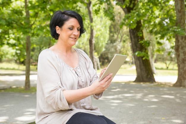 Gelukkige vreedzame vrouw die internet raadpleegt
