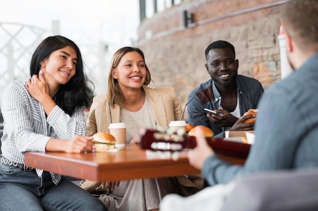Gelukkige vrienden aan tafel met hamburgers