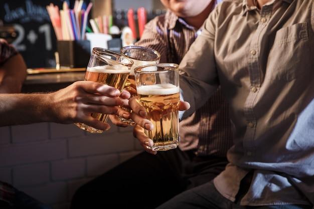 Gelukkige vrienden die bier drinken bij teller in bar