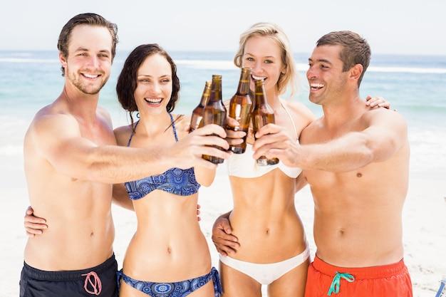 Gelukkige vrienden die bierflessen op het strand roosteren