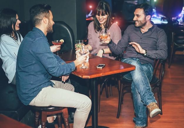 Gelukkige vrienden die cocktails binnen jazzcocktailbar drinken