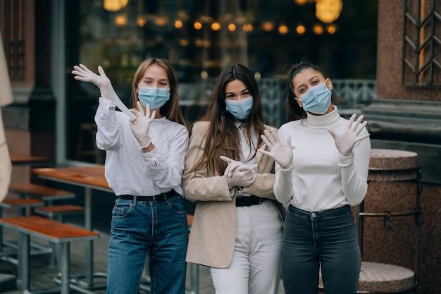 Gelukkige vrienden die de camera bekijken die beschermend gezichtsmasker draagt