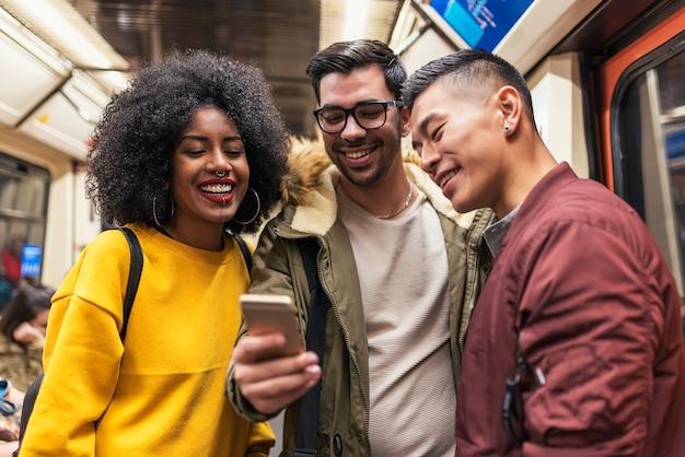 Gelukkige vrienden die de mobiel in de wagen van de trein gebruiken. vriendschapsconcept.