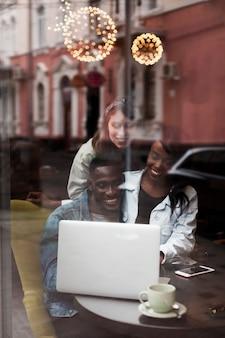 Gelukkige vrienden die dichtbij venster werken