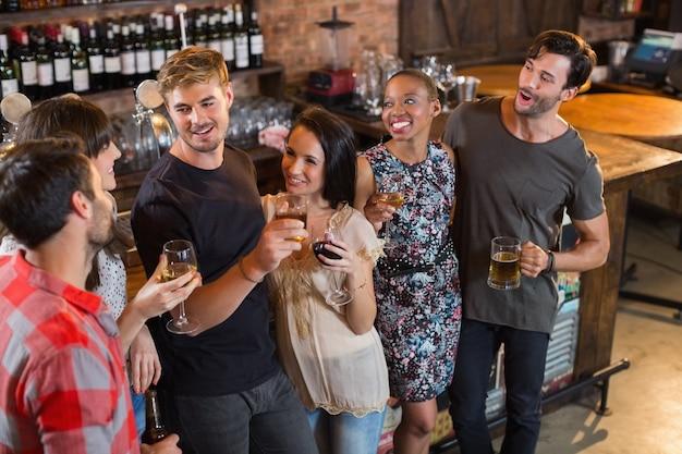Gelukkige vrienden die drankjes in staaf houden