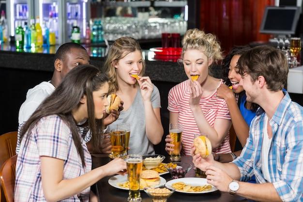 Gelukkige vrienden die een drank en een hamburger hebben