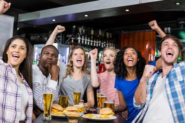 Gelukkige vrienden die een drank hebben en op sport letten