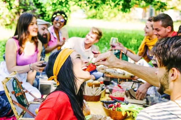 Gelukkige vrienden die een picknick in de tuin maken openlucht