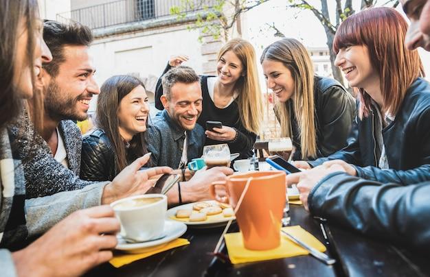 Gelukkige vrienden die en pret met mobiele slimme telefoons spreken hebben bij restaurant het drinken cappuccino