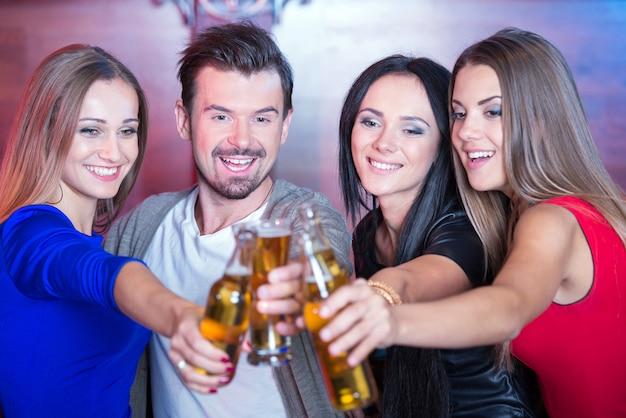 Gelukkige vrienden die glazen met cocktails in bar houden.