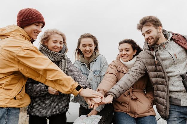 Gelukkige vrienden die handen samenbrengen