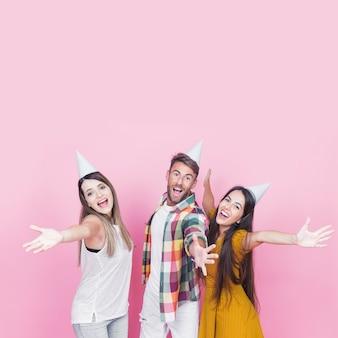 Gelukkige vrienden die hun handen op roze achtergrond outstretching