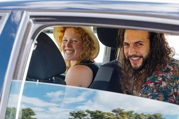 Gelukkige vrienden die in auto tijdens einde op de zomerdag zitten