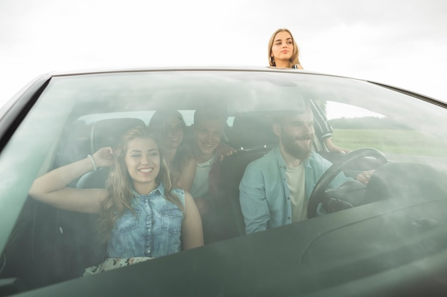 Gelukkige vrienden die in de auto genieten van