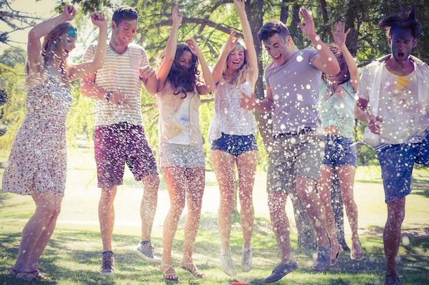 Gelukkige vrienden die in de waterspruit springen