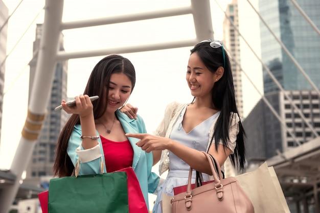 Gelukkige vrienden die in stad winkelen
