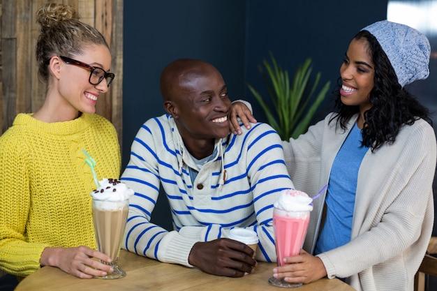 Gelukkige vrienden die koffie en milkshakes in koffie hebben