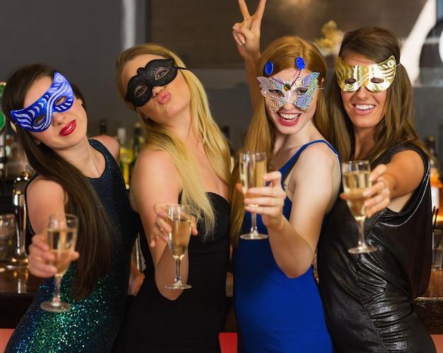 Gelukkige vrienden die maskers dragen die champagneglazen tonen