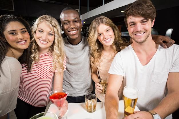 Gelukkige vrienden die met bier en cocktails roosteren