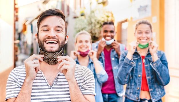Gelukkige vrienden die met geopende gezichtsmaskers glimlachen na sluiting heropening