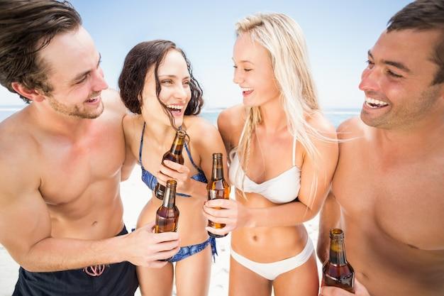 Gelukkige vrienden die op het strand genieten van