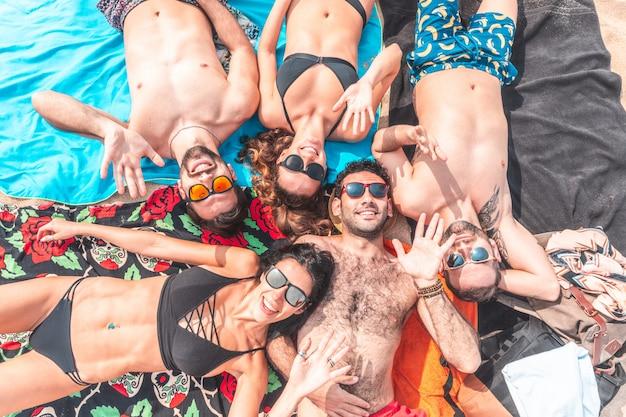 Gelukkige vrienden die op het strand in barcelona ontspannen