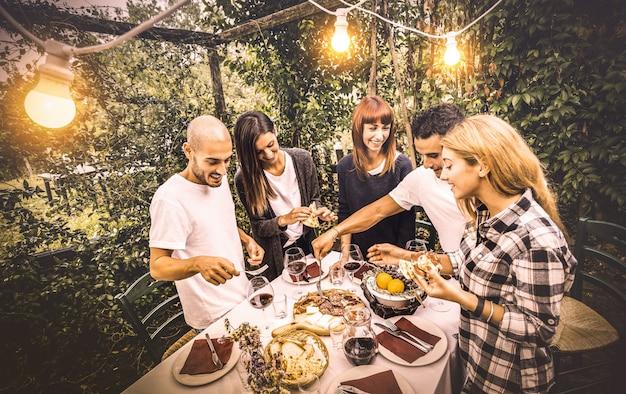 Gelukkige vrienden die plezier hebben met het eten van lokaal eten op het tuinfeest