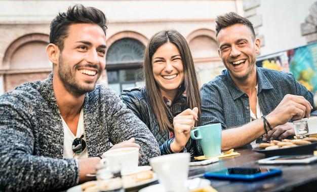Gelukkige vrienden die praten en plezier hebben in het café-restaurant dat cappuccino en hete thee drinkt