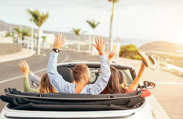 Gelukkige vrienden die pret in convertibele auto hebben bij zonsondergang in vakantie