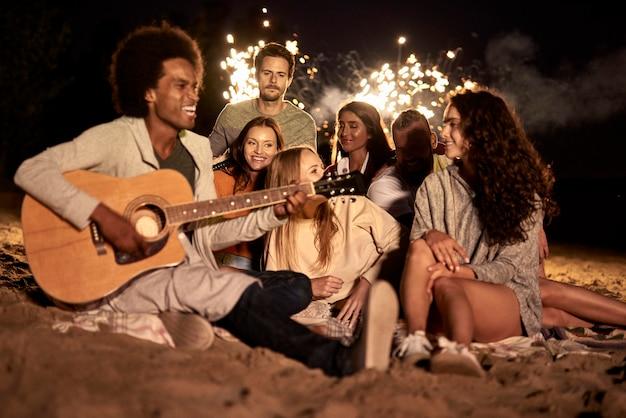 Gelukkige vrienden die 's nachts plezier hebben op het strand