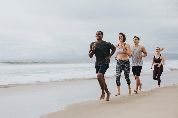 Gelukkige vrienden die samen joggen op het strand