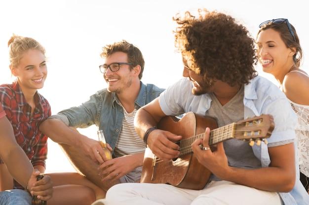 Gelukkige vrienden die samen plezier hebben terwijl de kerel gitaar speelt