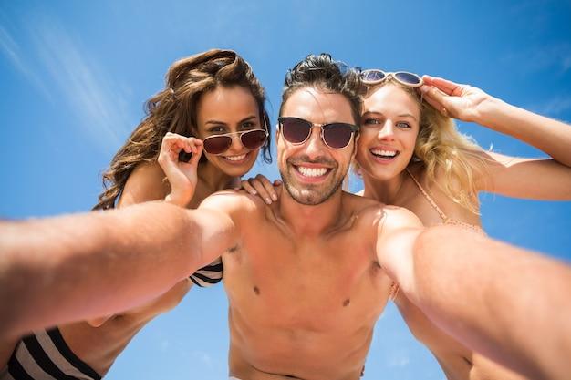Gelukkige vrienden die selfie op het strand nemen