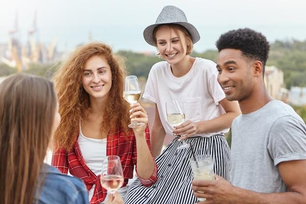 Gelukkige vrienden die stijlvolle kleding dragen die afstuderen vieren