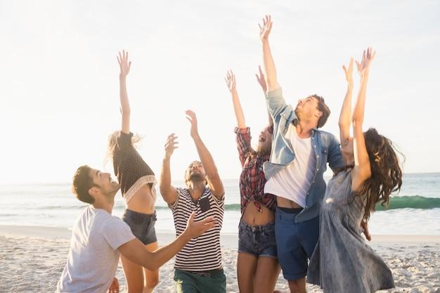 Gelukkige vrienden die strandvolleyball spelen