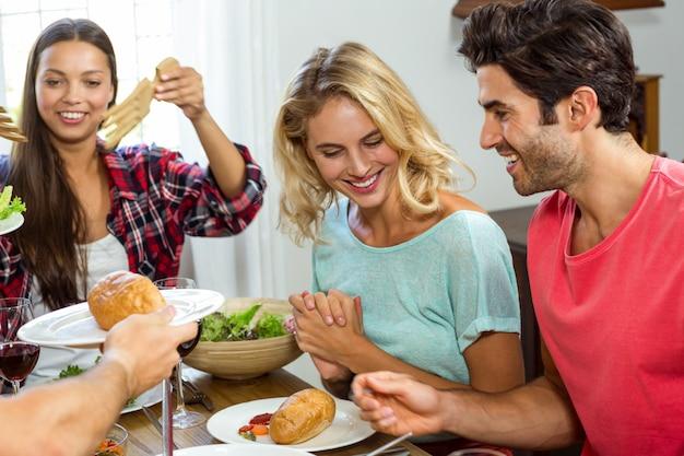 Gelukkige vrienden die terwijl het hebben van lunch glimlachen
