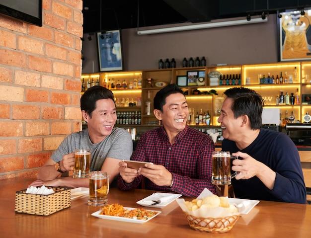 Gelukkige vrienden die tijd samen doorbrengen in een bierbar