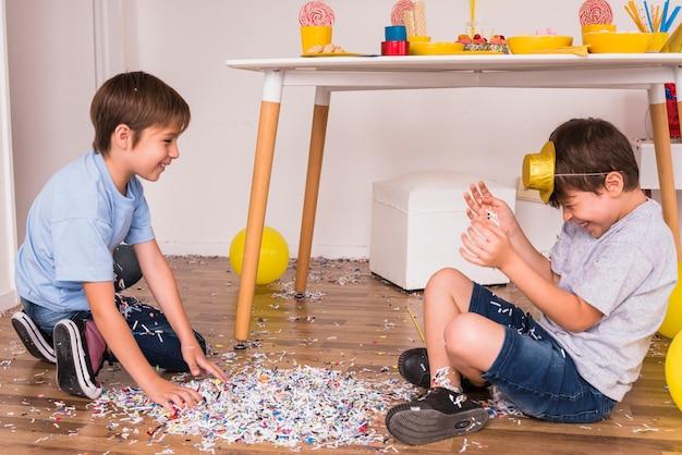 Gelukkige vrienden die van partij met confettien genieten