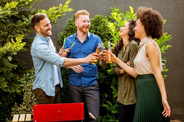 Gelukkige vrienden die voedsel roosteren en van barbecuepartij in openlucht genieten